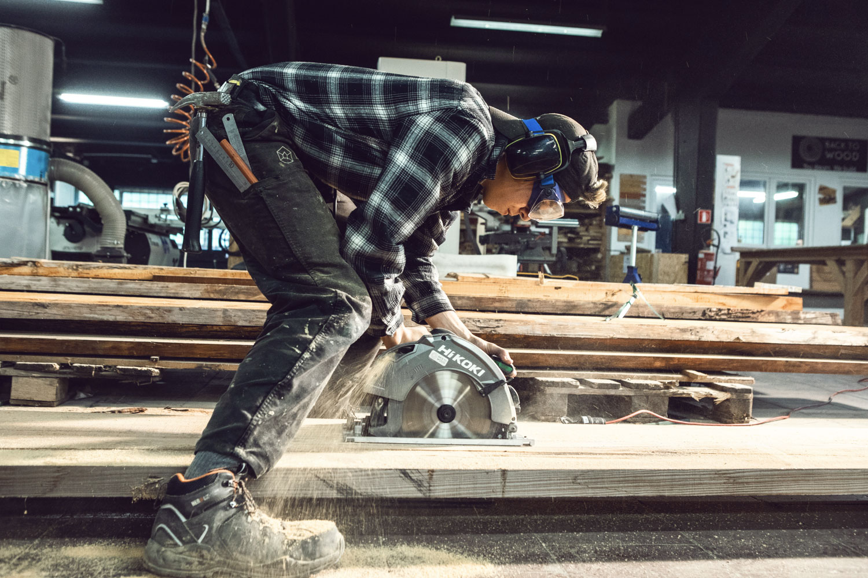 Un ouvrier découpe une planche de bois au sol